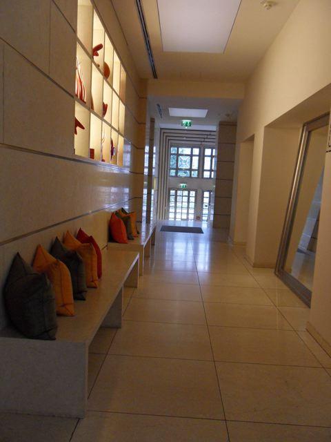 Este é o corredor entre a entrada do prédio e a recepção. Não sei se alguém senta nesses banquinhos, mas achei bonitinha a combinação de almofadas com o bege.