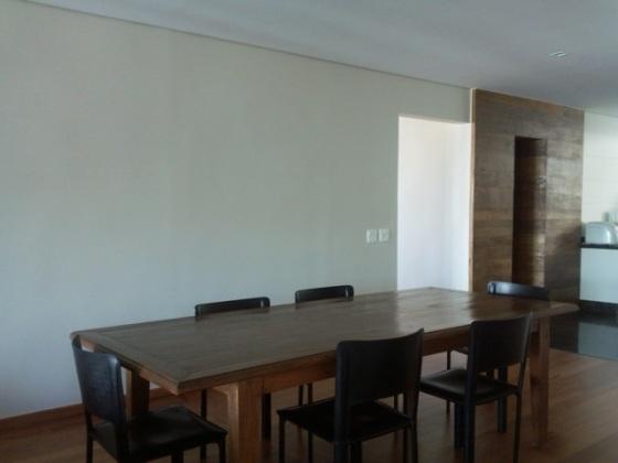 mesa de jantar de madeira e cadeiras pretas de couro