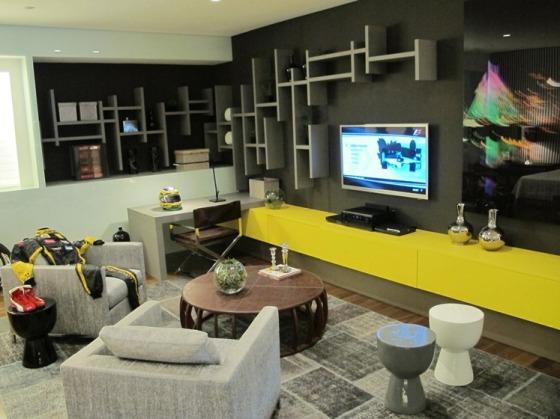 Projeto usou o amarelo na bancada da TV, o que deixou o ambiente sofisticado e alegre, apesar de masculino