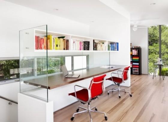 Parede de vidro suporta prateleira e bancada de madeira. Aproveitamento de espaço é diferencial do escritório