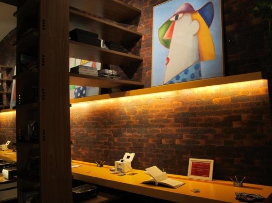 Escritório ganhou ar de modernidade com bancada amarela, tijolos aparentes e madeira