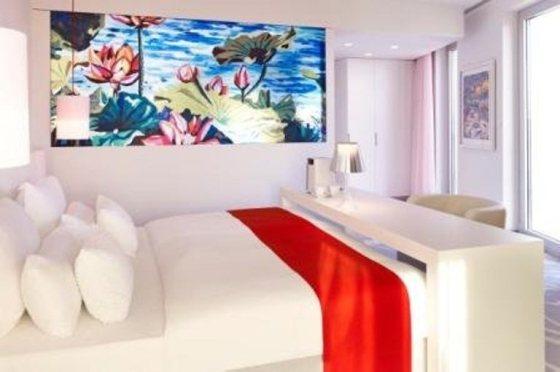 Quarto branco com detalhes em vermelho permitem que obras de arte se valorizem