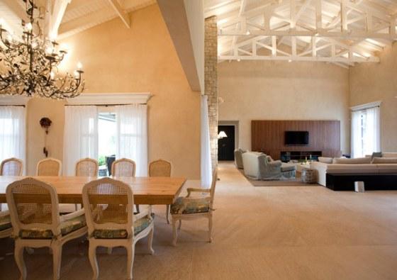 Novamente, janelas amplas, cortinas brancas de estampados claros nas cadeiras amenizam o peso da mesa de madeira e da textura na parede