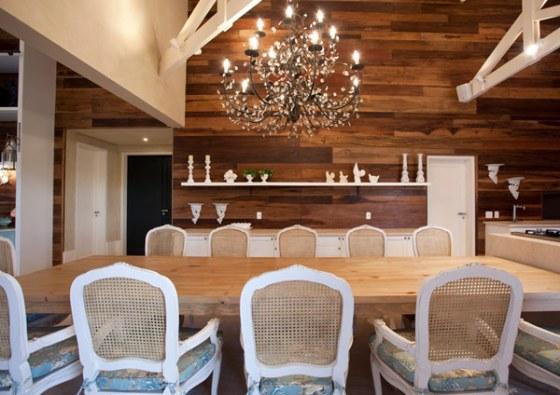 Novamente, janelas amplas, cortinas brancas de estampados claros nas cadeiras amenizam o peso da mesa de madeira e do painel de madeira na parede