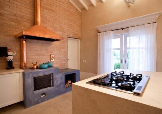 Projeto preservou simplicidade, frisada por fogão à lenha com cimento queimado e coifa de bronze