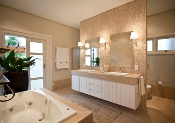 Mármore, hidromassagem branca, espelhos e pedra nas paredes reforçam estilo clean e amplitude