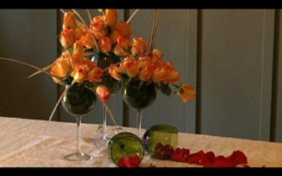 Rosas em taças de vinho de diferentes alturas criam ambiente romântico e original