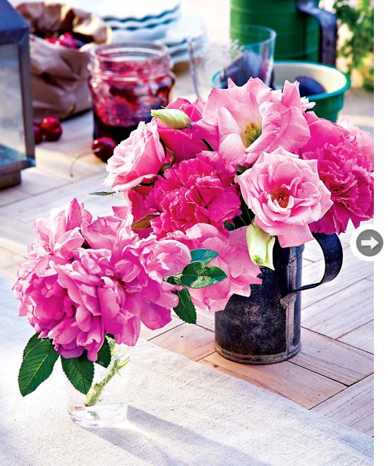 Toalha de linho e mesa de madeira complementam o visual do arranjo de flores feito em um bule