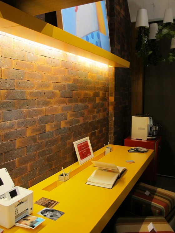 Bancada amarela, marcenaria e tijolos aparentes são complementados por geladeira retrô
