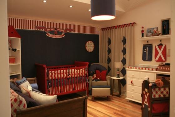 Cores azul e vermelho estão em papel de parede, berço, almofadas e poltronas