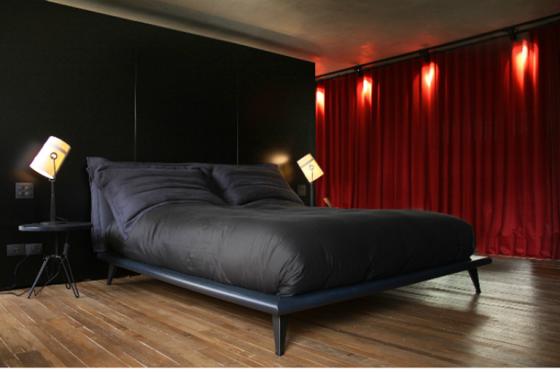 Quarto masculino com cama, parede e cabeceira preta