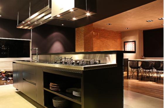 Cozinha integrada à sala em tons de preto e metais deixou o apartamento sofisticado