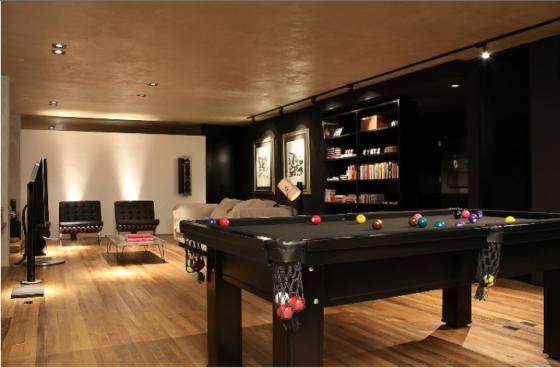 Sala preta é aquecida por objetos como livros, bolas de sinuca e chão de madeira. Teto cinza, parede branca e sofá bege criam sensação de tom sobre tom