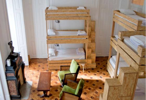 Camas em madeira e luminárias de ferro em formato de lâmpada modernizam quarto