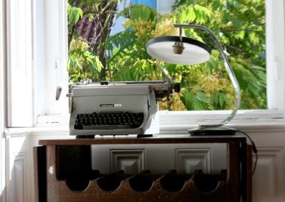 estante de madeira desgastada, máquinha de escrever e luminária antiga