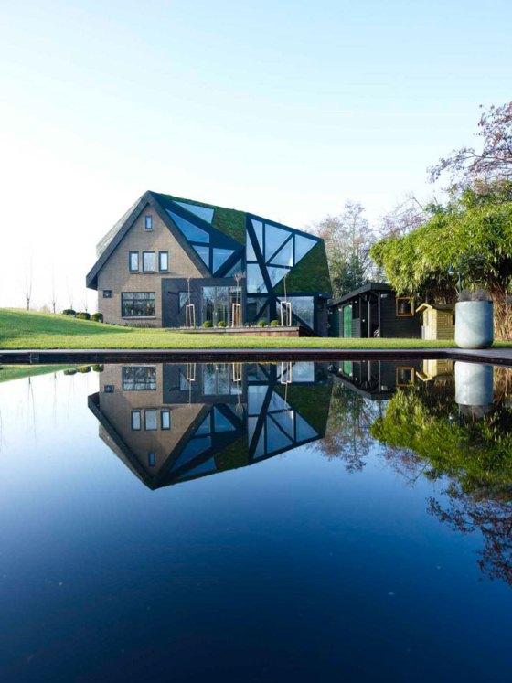 Projeto de casa com telhado verde e ripas de madeira é do escritório escritório Ooze, com base em Paris e Roterdã