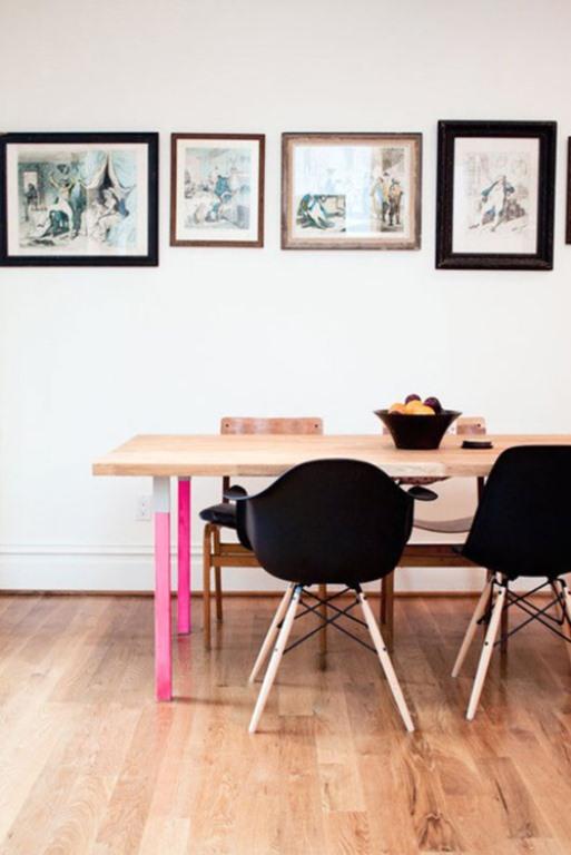 sala de jantar ficou moderna com mesa em madeira clara, pés rosa neon e cadeiras pretas