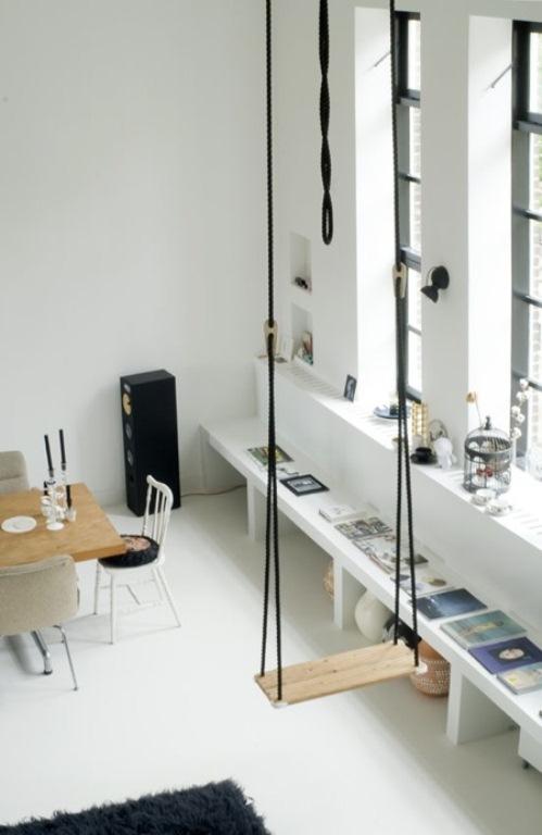 sala branca com pé direito alto, prateleiras e trapézio