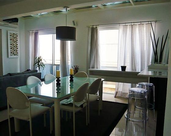 Chão e paredes brancas, móveis modernos e cozinha americana