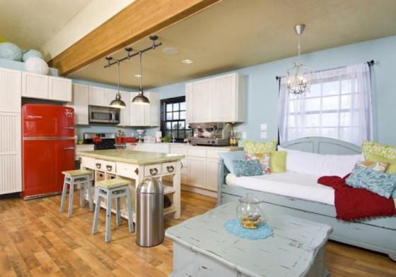 Sofá de madeira azul com mesa de centro azul contrastam com geladeira vermelha e luminárias industriais