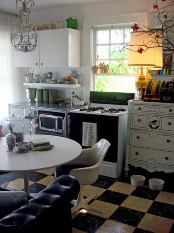 Sofá preto de couro na cozinha, que tem chão quadriculado em branco e preto e móveis rústicos de madeira
