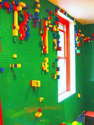 Quarto infantil com base de lego verde na parede, em que criança pode montar peças