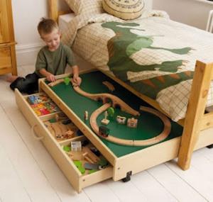 Cama infantil com gavetas que se transformam em espaço para a criança brincar e montar quebra-cabeças. Na prateleira de baixo as outras peças ficam guardadas