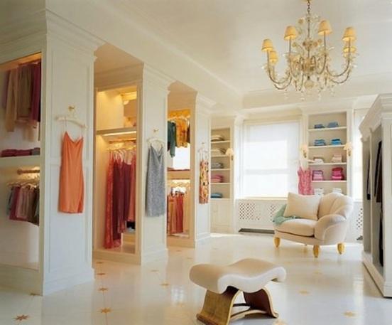 Closet em apartamento espaçoso, com poltrona, prateleiras e luminária
