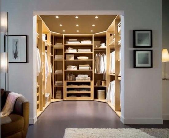 Quarto extra revertido em closet de madeira com prateleiras, poltrona e iluminação